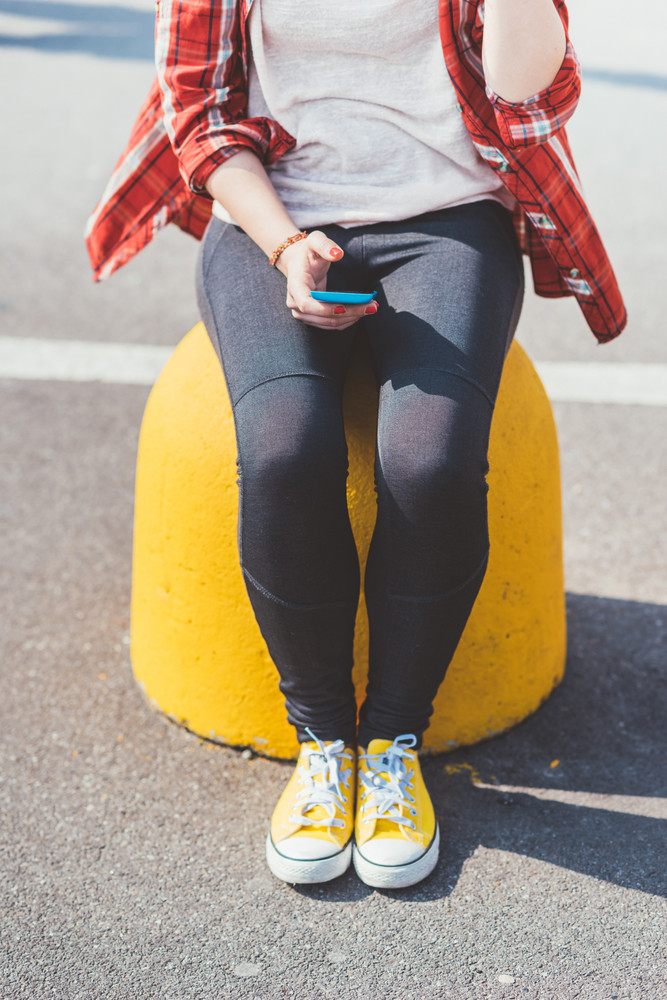 From the neck down view of young woman sitting outdoor in the city using a smart phone hand hold - technology, social network, communication concept