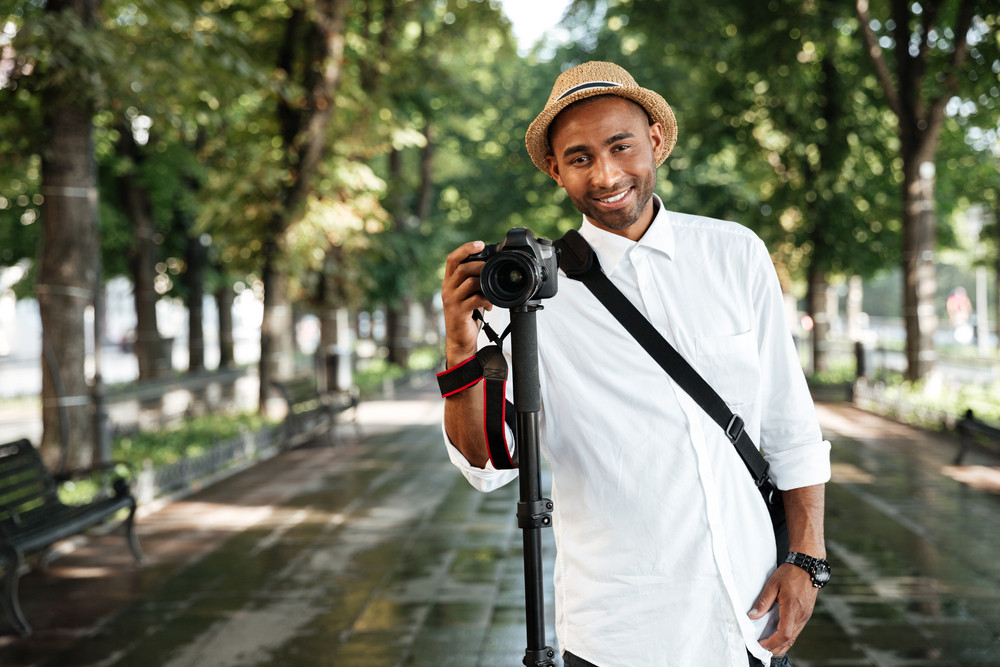 Front portrait of black man in park. with camera