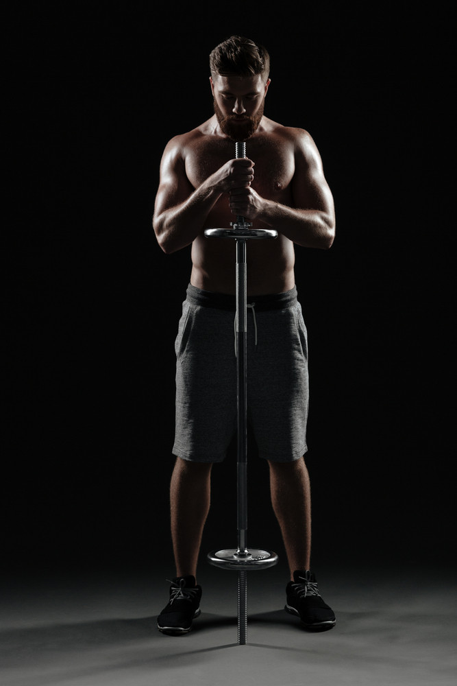 Front portrait of naked athletic man with barbell. full length image. isolated dark background