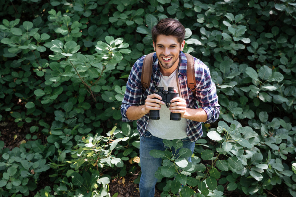 Front view of man with binoculars in forest. from above image