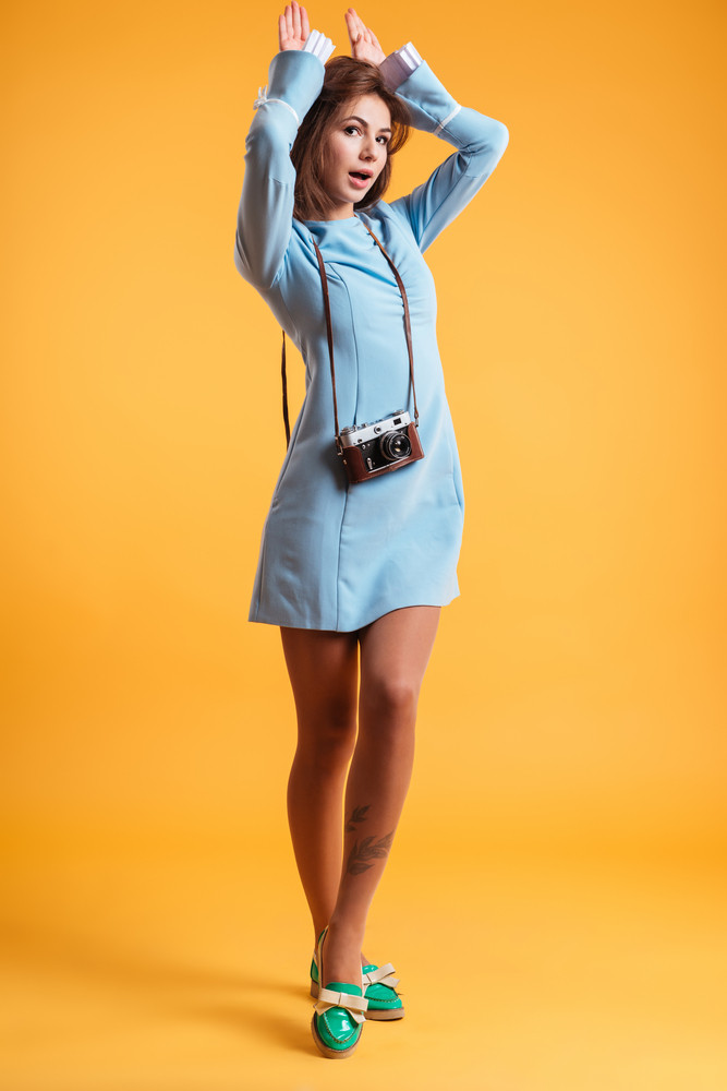 Full lebgth of smiling playful young woman with old vintage camera making ears by hands over yellow background
