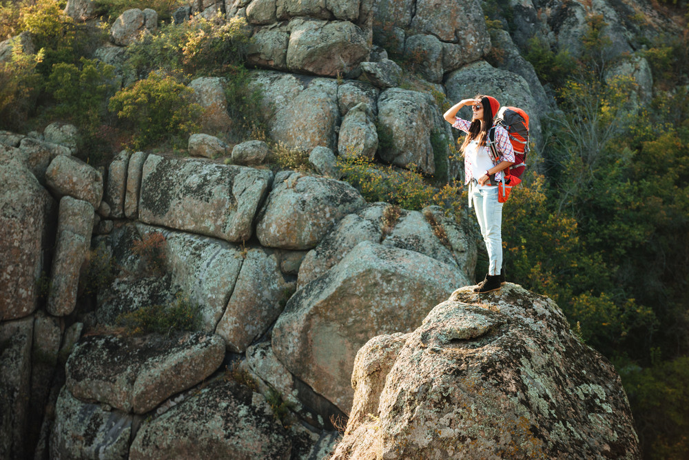Full length adventure woman near the canyon. on rock