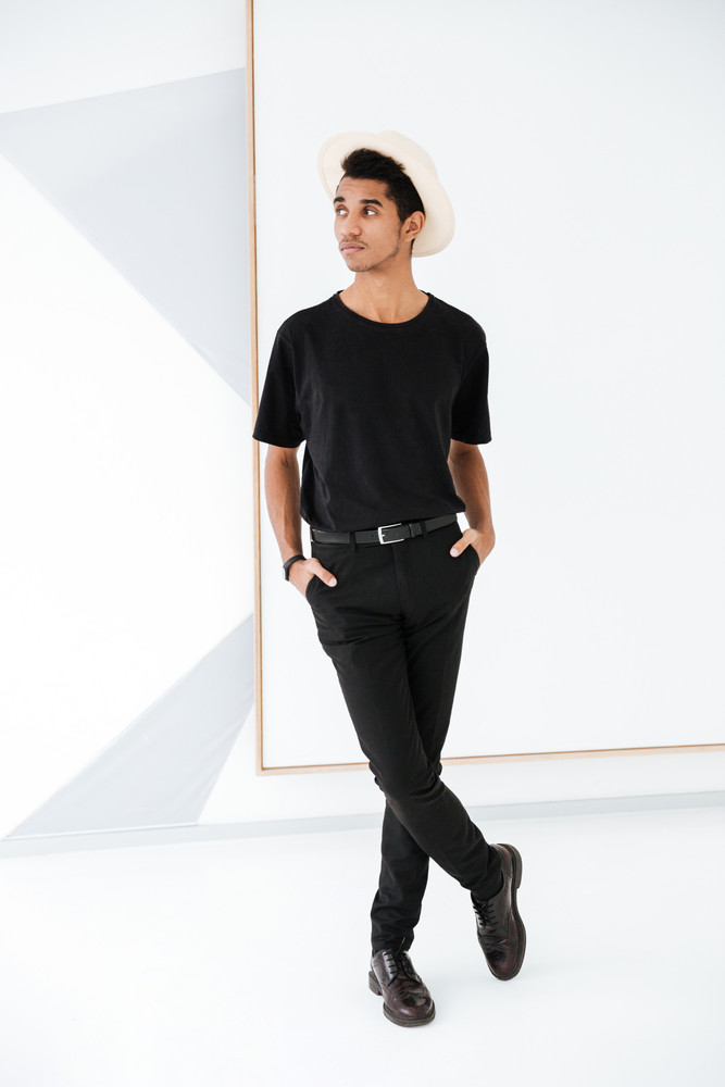 Full length african man in black clothing and hat posing in office and looking away