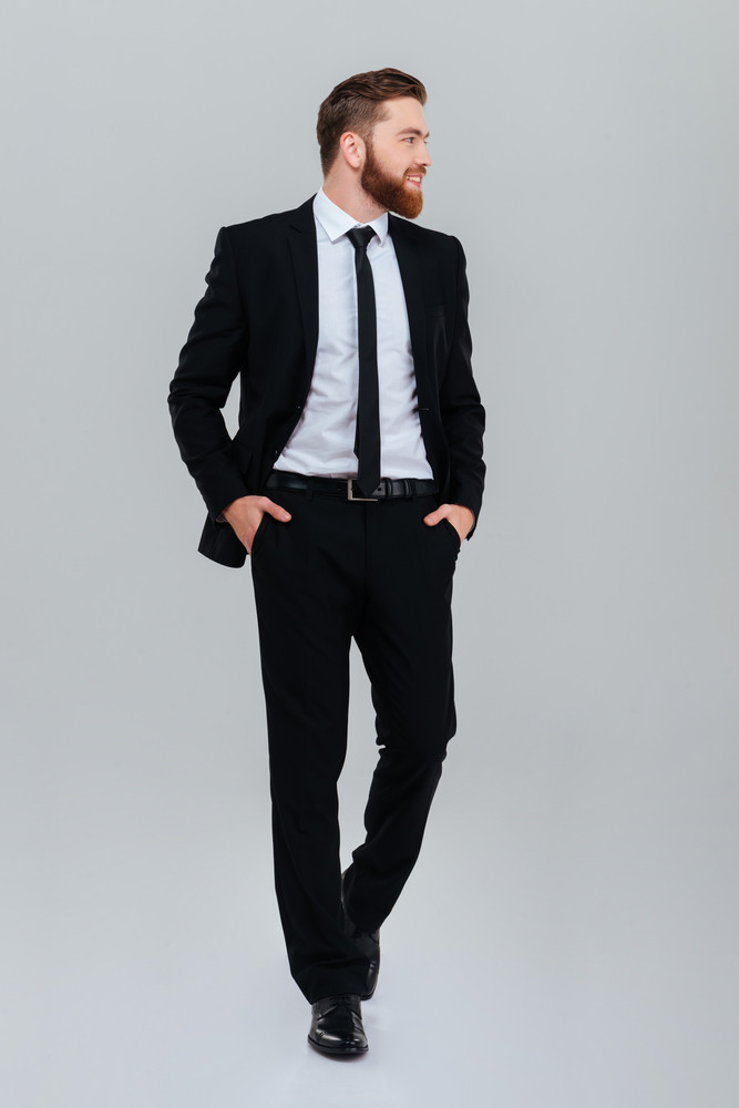 Full length bearded business man in black suit with hands in pockets looking aside in studio. isolated gray background