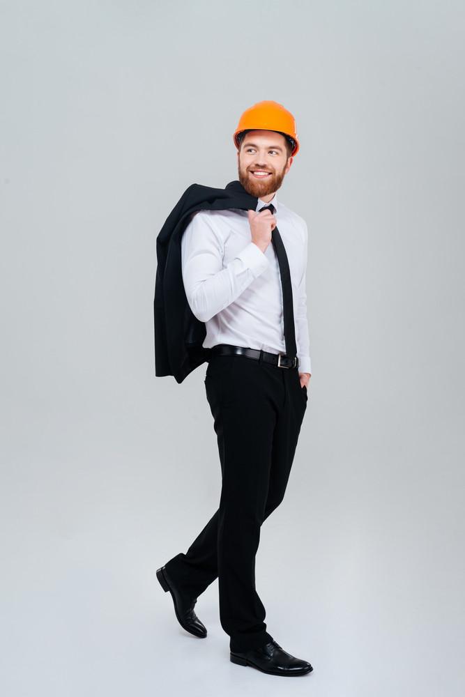 Full length bearded engineer standing sideways in orange helmet with jacket on shoulder. Isolated gray background