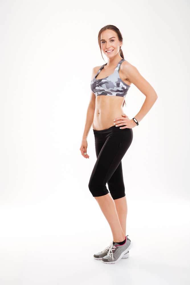 Full length fitness woman in studio. stands sideways. looking at camera