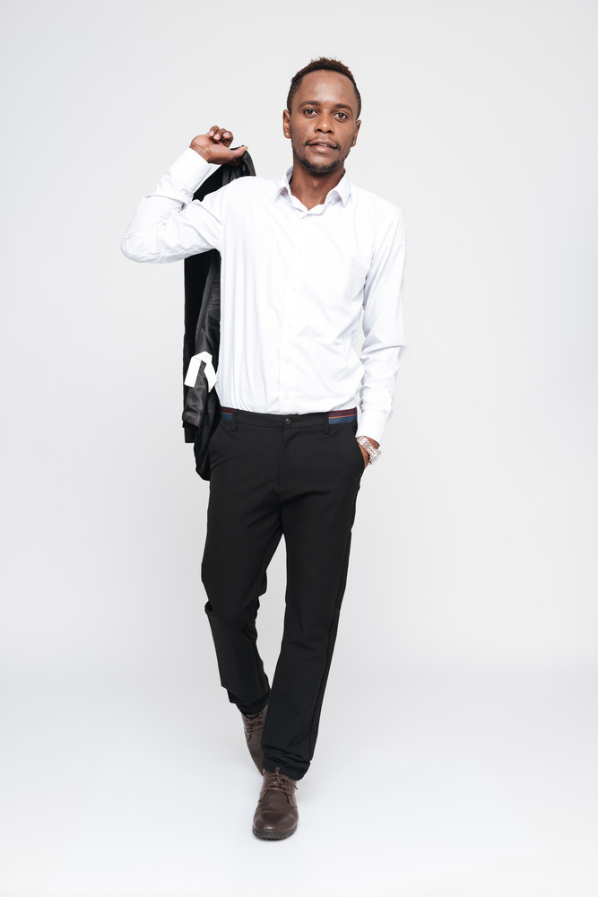Full length image of cool african man in shirt with arm in pocket. Isolated white background