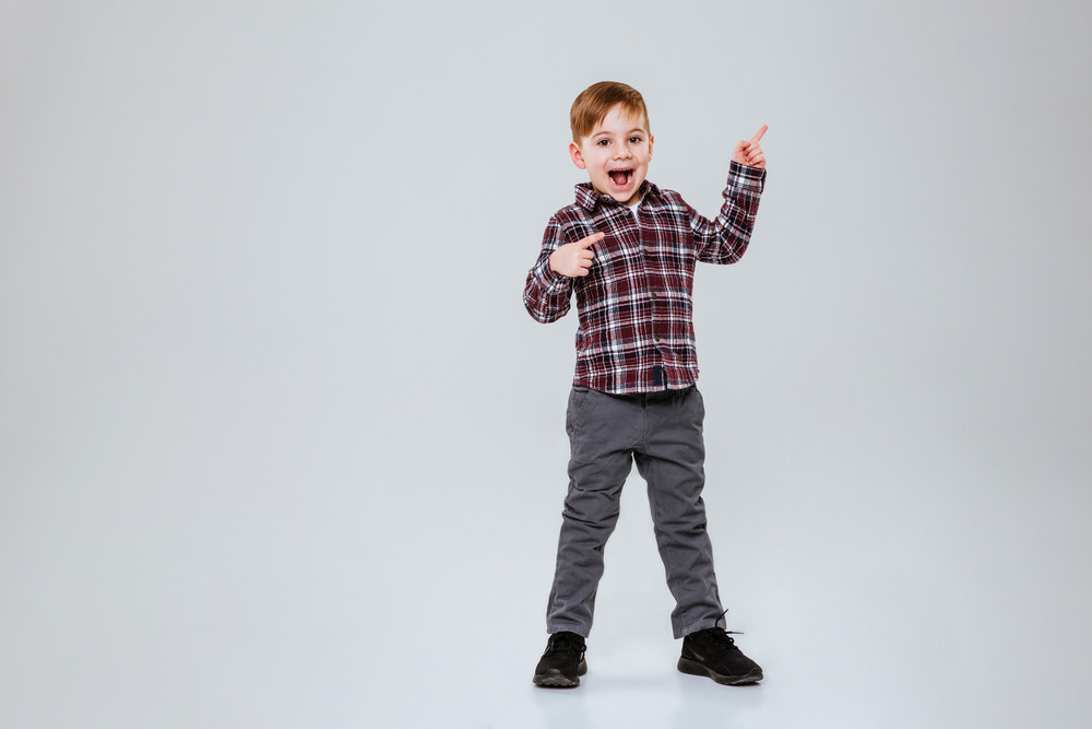 Full length image of funny young boy with open mouth. Isolated gray background
