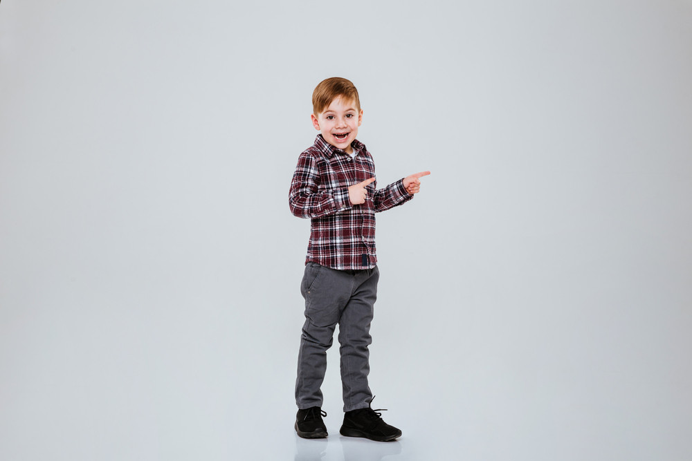 Full length image of young boy in studio. Isolated gray background