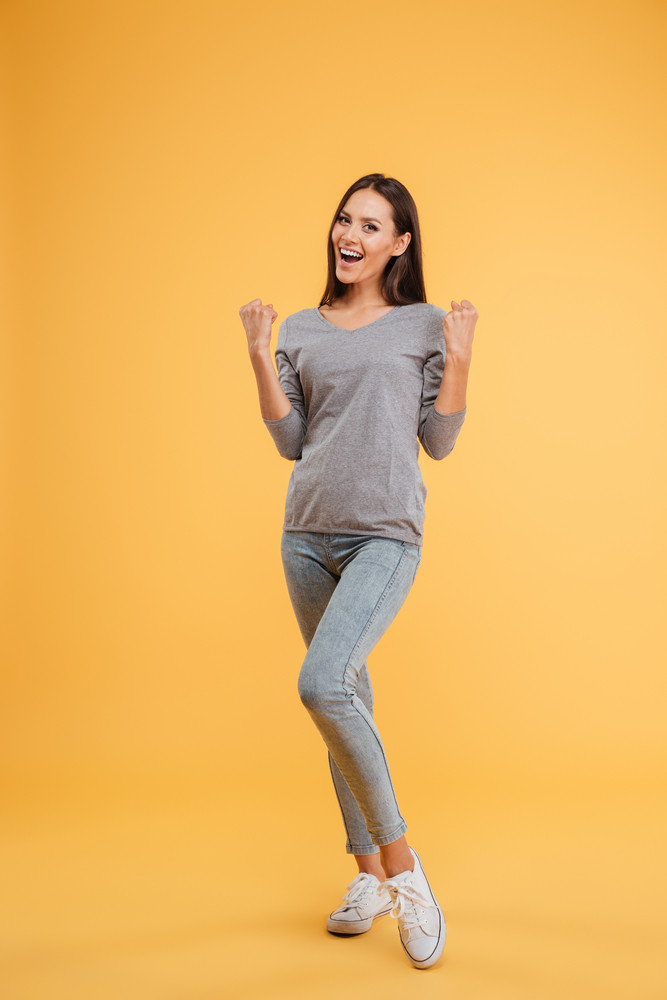Full length laughing model in studio. looking at camera. isolated orange background