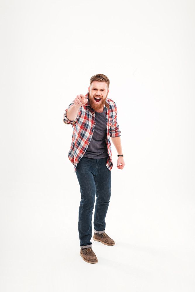 Full length of a bearded casual man in plaid shirt pointing at camera isolated on a white background