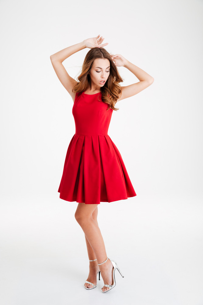 Full length of a pretty brunette woman in red dress posing with raised hands isolated over white background