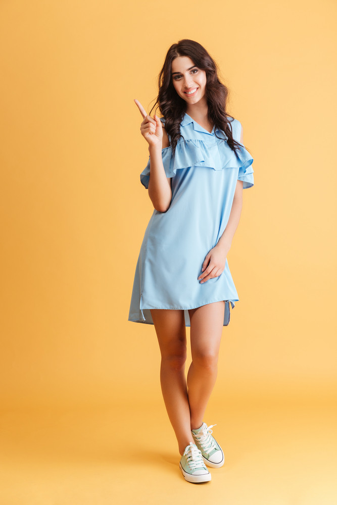 Full length of a smiling happy woman in blue dress pointing finger up over orange background