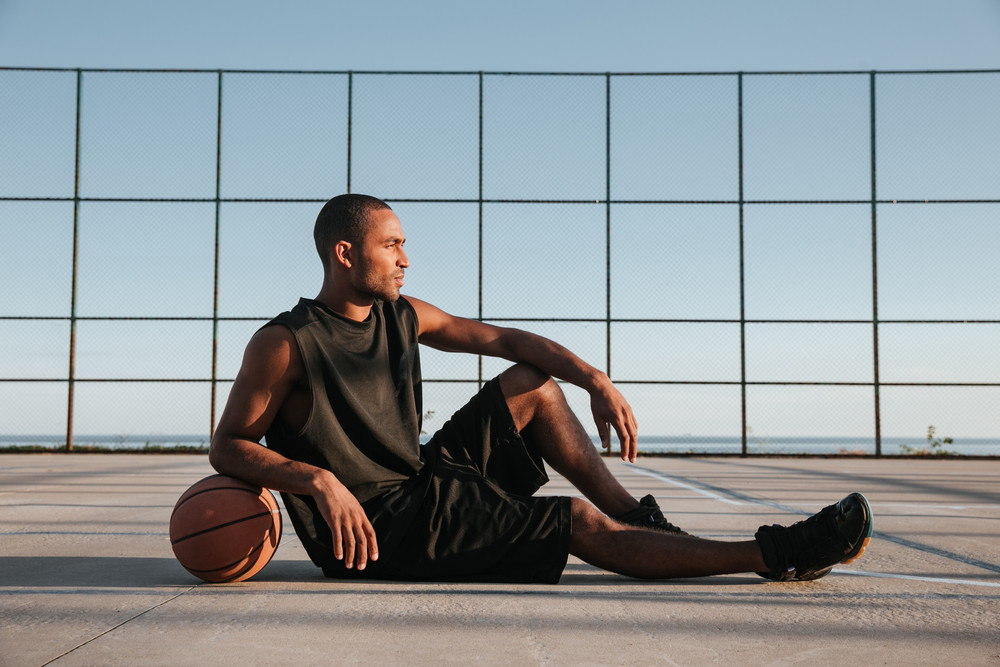 Full length of african sportsman resting at the playground with basketball