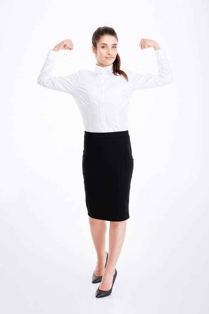 Full length of attractive young businesswoman standing and showing biceps