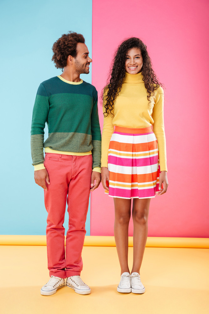 Full length of cheerful beautiful african young couple standing over colorful background