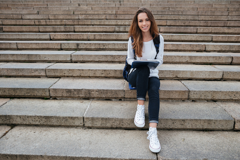 Full length of cheerful cute young woman with backpack and noteped sitting on stairs outdoors