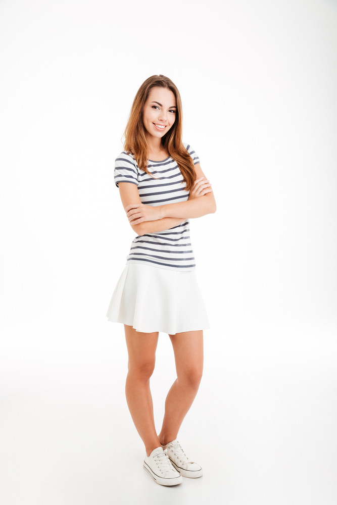 Full length of cheerful pretty young woman standing with arms folded over white background