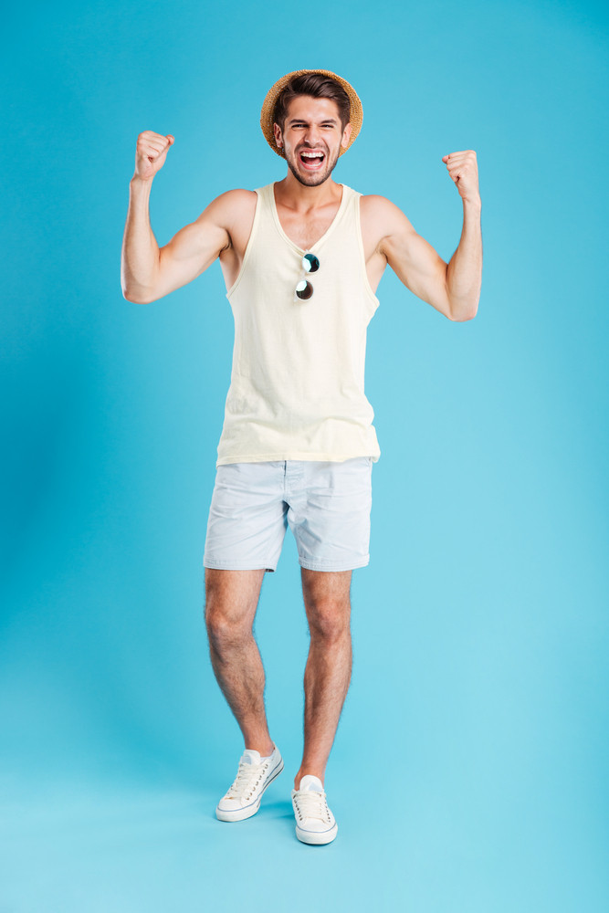 Full length of cheerful young man in hat and shorts standing and celebrating success over blue background