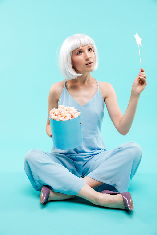 Full length of cute young woman with marshmallows and magic wand sitting
