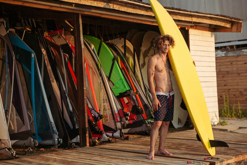 Full length of handsome curly man surfer standing and holding yellow surfing board