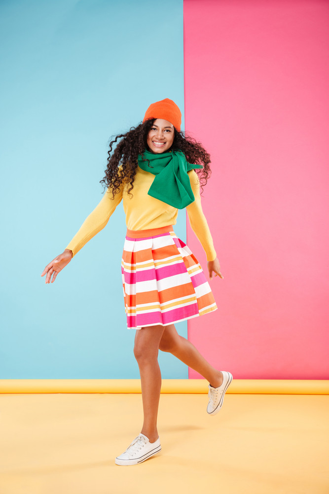 Full length of happy african american young woman in hat and scarf smiling and running