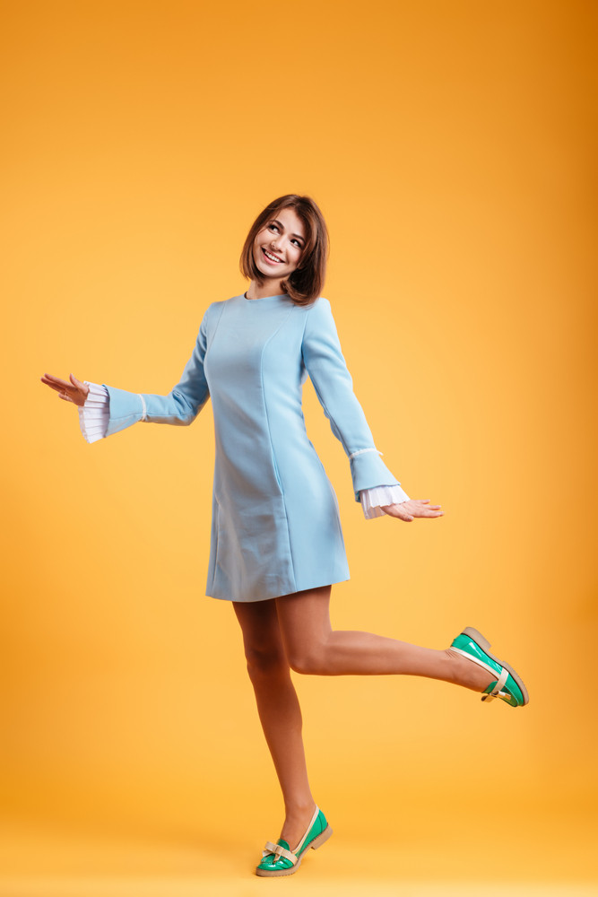 Full length of happy charming young woman smiling and dancing over yellow background