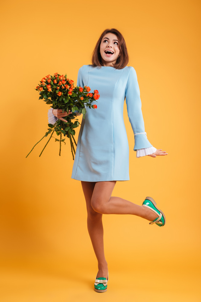 Full length of happy excited young woman standing holding bunch of flowers over yellow background