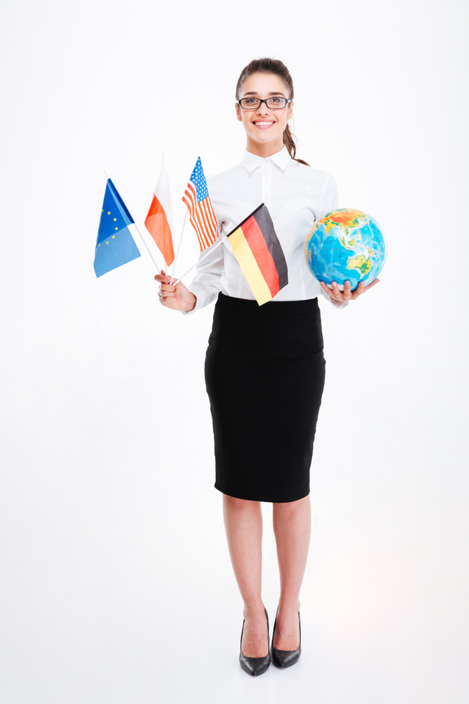 Full length of happy young businesswoman in glasses holding flags of several countries and earth globe
