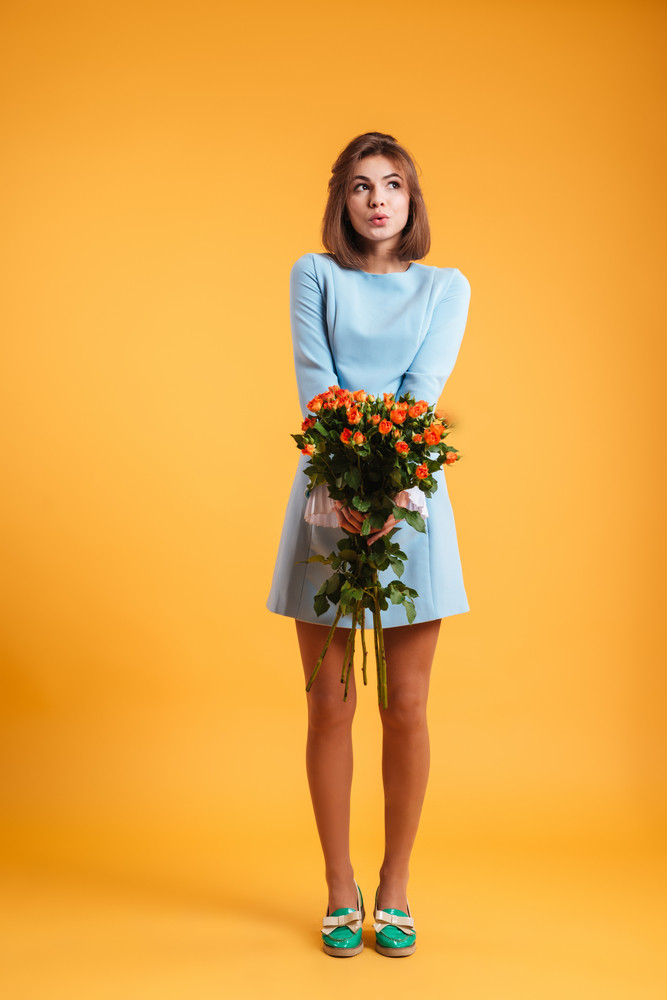 Full length of pensive lovely young woman standing and holding bunch of roses over yellow background