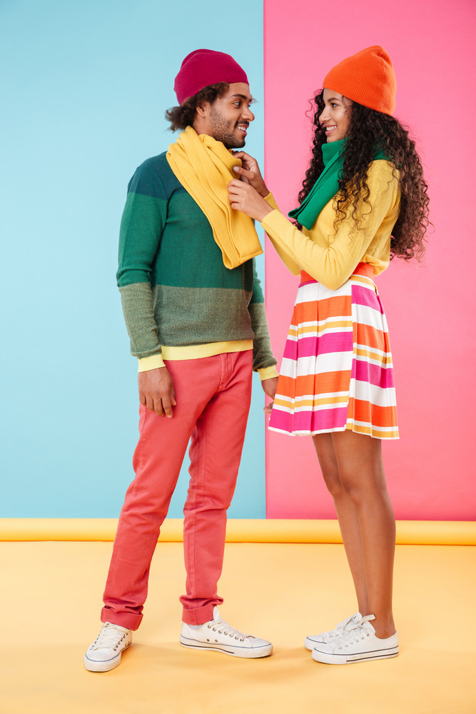 Full length of smiling african american young couple wearing scarves and hats