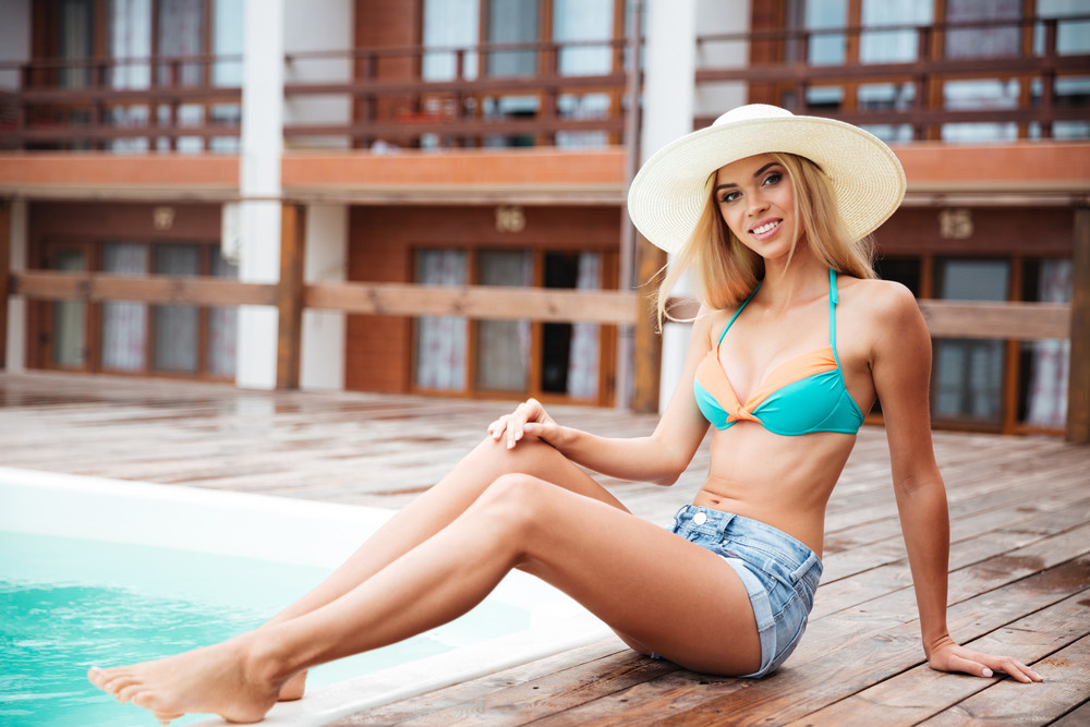 Full length of smiling beautiful young woman in hat sitting near swiming pool