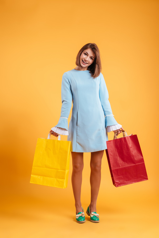 Full length of smiling cute young woman with shopping bags over yellow background