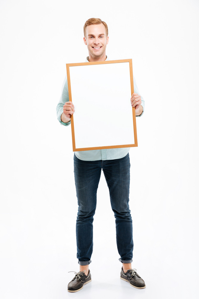 Full length of smiling young man holding blank whiteboard over white background