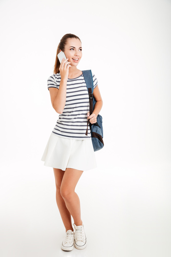 Full length portrait if a happy female student talking on the phone and looking away isolated on a white background