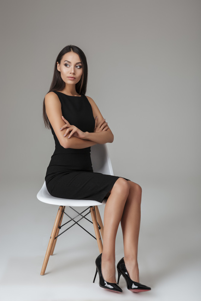 Full length portrait of a beautiful smart woman sitting on the chair with arms folded over gray background