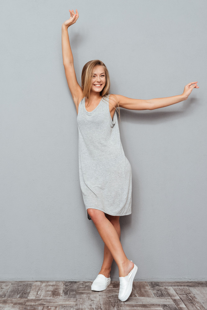 Full length portrait of a beautiful smiling woman in dress posing isolated on a gray background