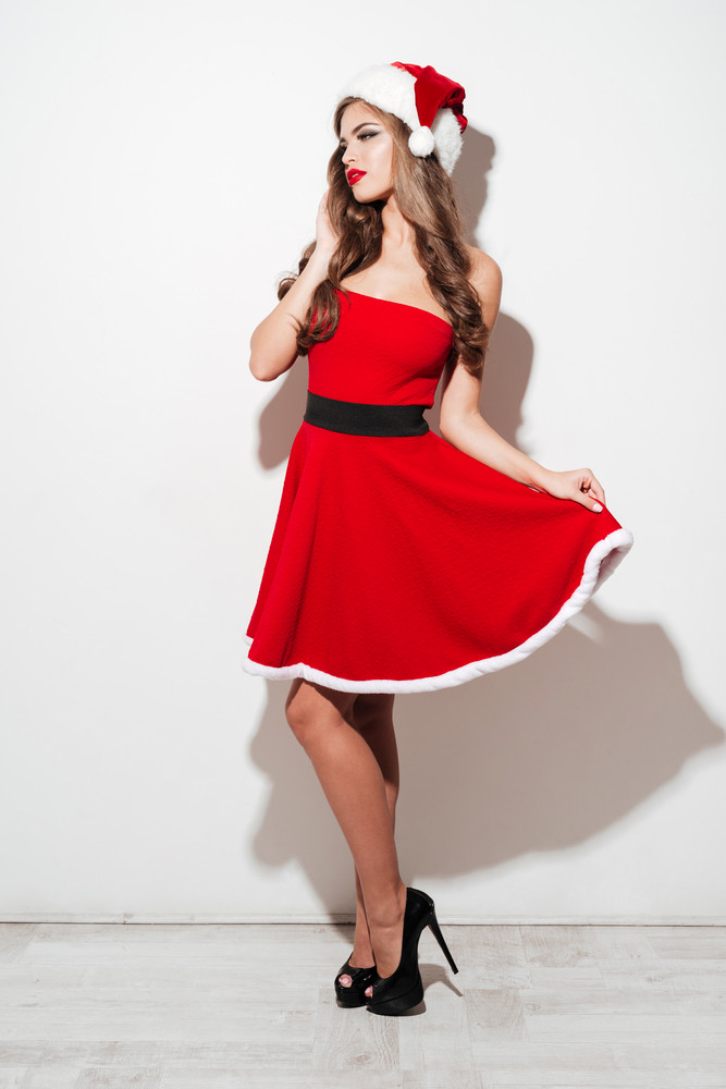 Full length portrait of a beautiful young woman in red santa claus dress posing and looking away isolated over white background