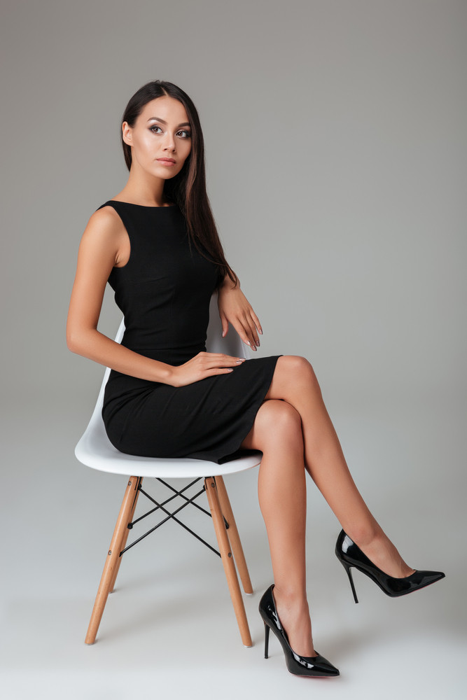 Full length portrait of a businesswoman in black dress sitting on the chair over gray background