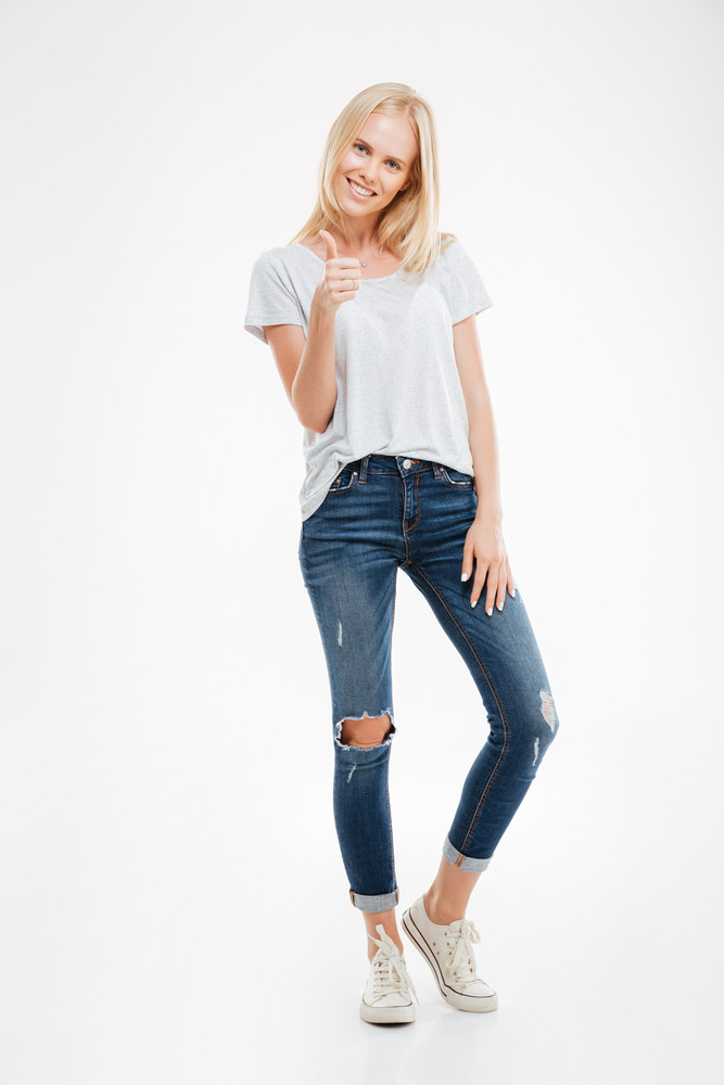 Full length portrait of a casual attractive blonde woman standing and showing thumbs up gesture isolated on a white background