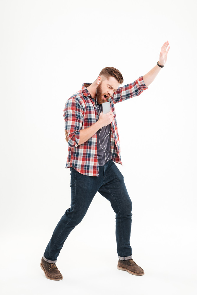 Full length portrait of a casual bearded man listening music and holding invisible microphone over white background