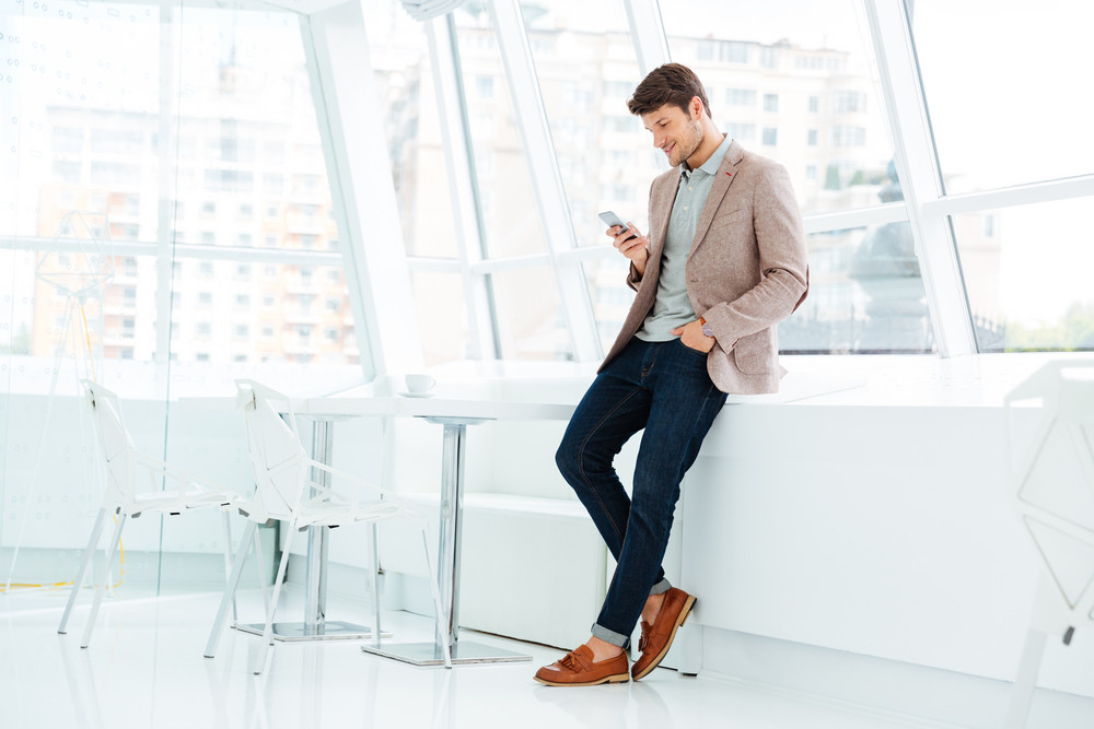 Full length portrait of a casual smiling businessman standing and using mobile phone indoors