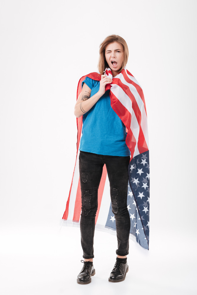 Full length portrait of a casual young girl holding usa flag and winking over white background