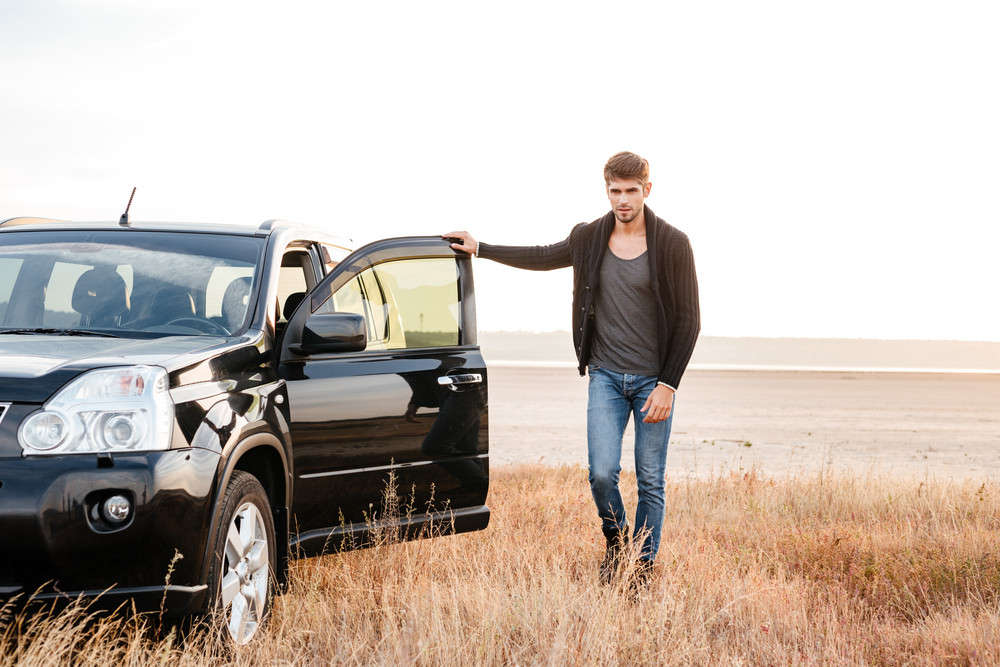 Full length portrait of a casual young man standing with his car parked outdoors