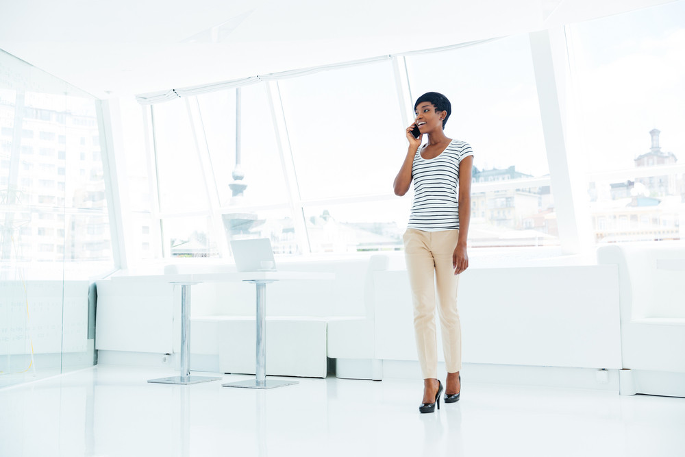 Full length portrait of a cheerful african american young businesswoman standing and talking on mobile phone in office