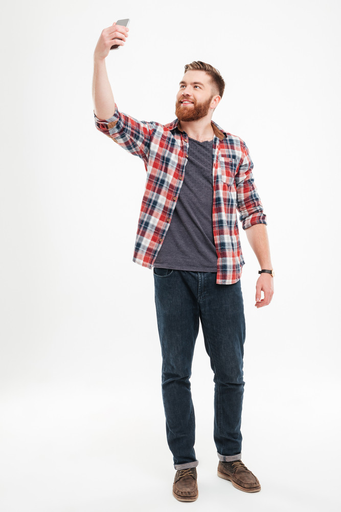 Full length portrait of a cheerful bearded man in plaid shirt taking selfie over white background