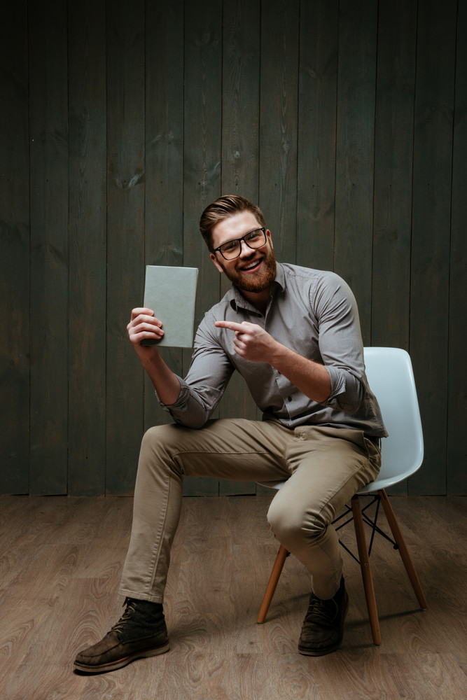 Full length portrait of a cheerful bearded man pointing finger at book cover while sitting on chair isolated on a black wooden background