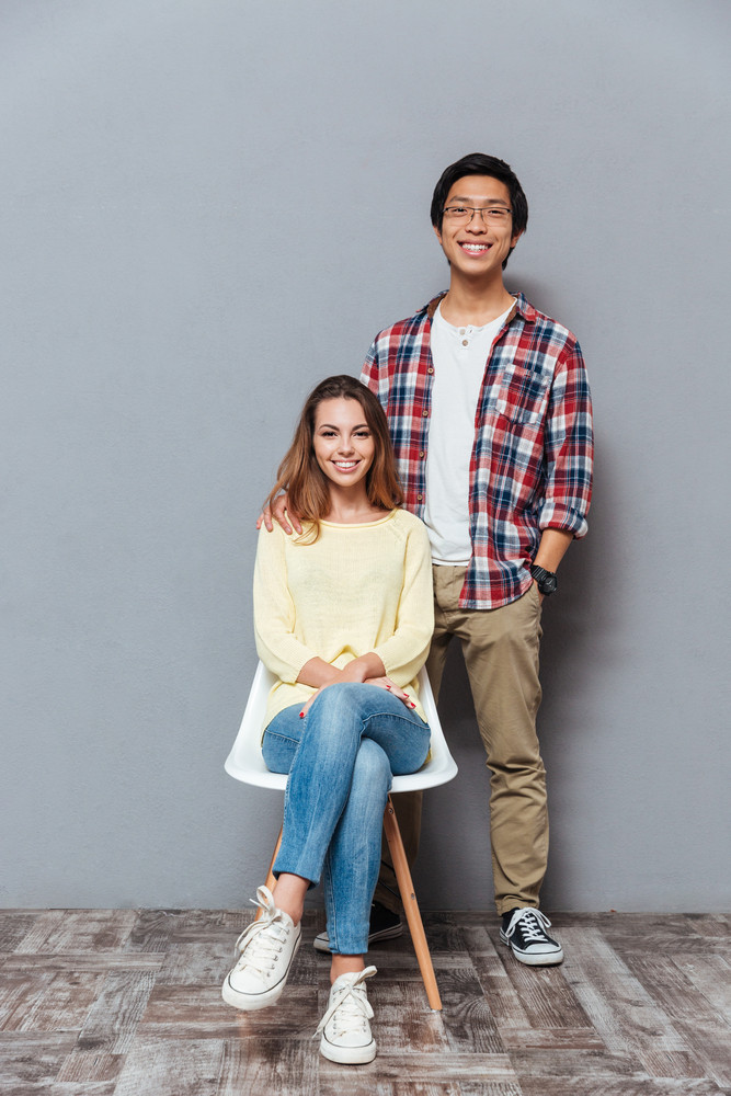 Full length portrait of a cheerful interracial couple standing and sitting isolated on the gray background