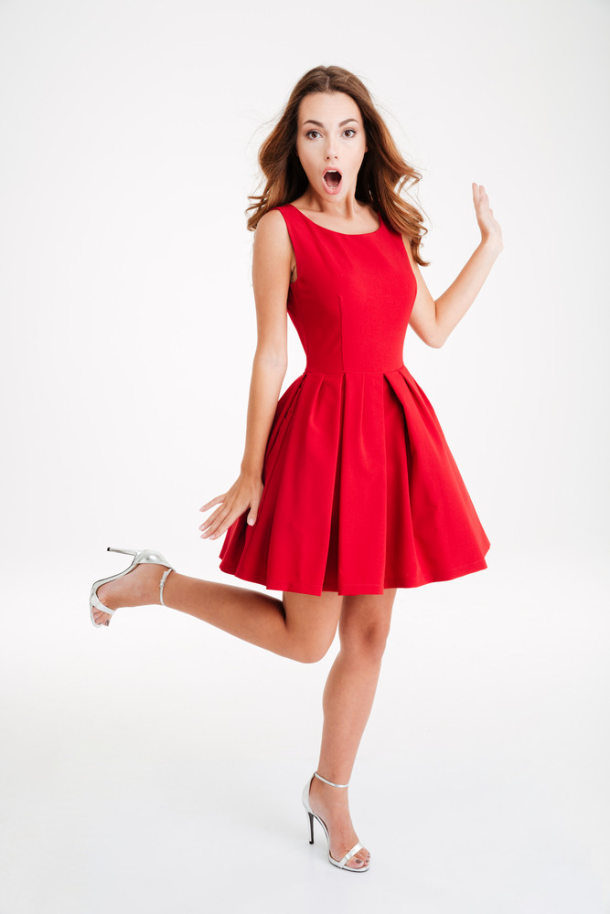Full length portrait of a cheerful surprised brunette woman in red dress posing on one leg isolated over white background