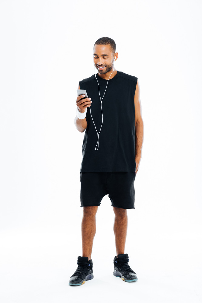 Full length portrait of a cheerful young african male athlete listening to music with earphones and cell phone over white background